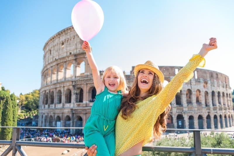 Madre e hija que animan con el globo rosado en Colosseum foto de archivo libre de regalías