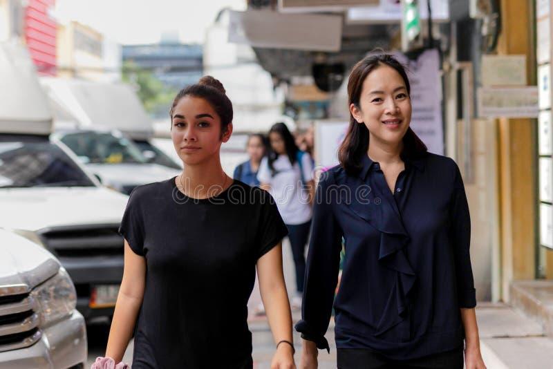 Madre e hija que caminan adentro en la calle que hace compras fotos de archivo