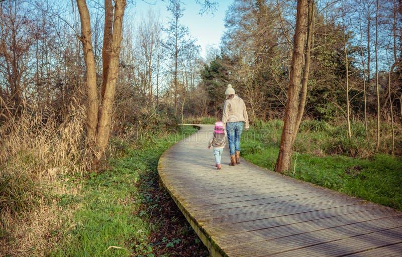 Madre e hija que caminan juntas llevando a cabo las manos imagenes de archivo