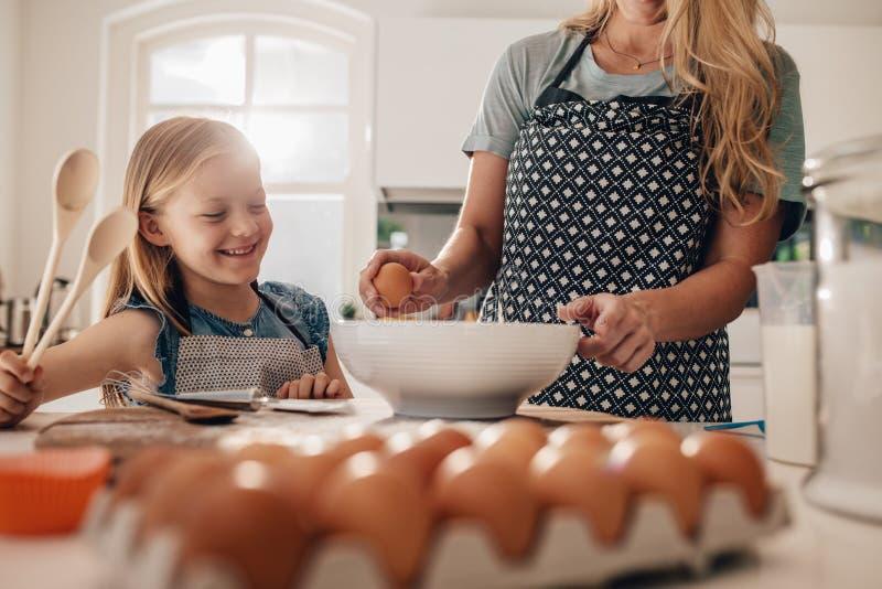 Madre e hija que cocinan junto en cocina imagenes de archivo