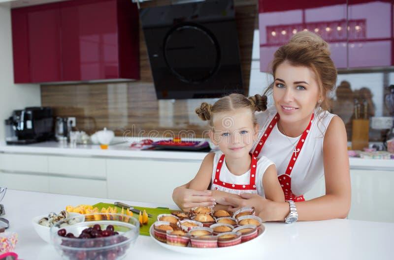 Madre e hija que cocinan las magdalenas en la tabla festiva fotografía de archivo