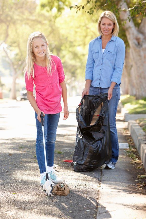 Madre e hija que cogen la litera en calle suburbana imagen de archivo