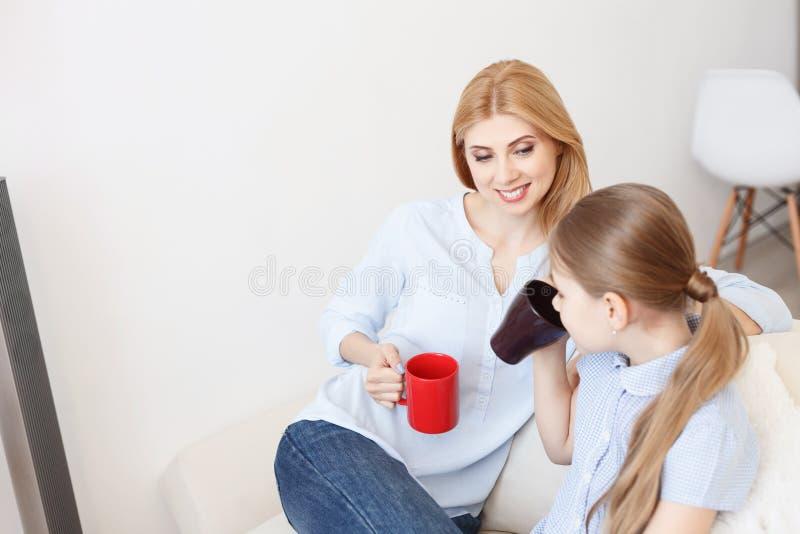 Madre e hija que comen té en el sofá imagen de archivo