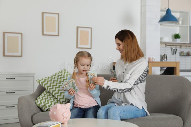 Madre e hija que cuentan el dinero en el sof? fotos de archivo