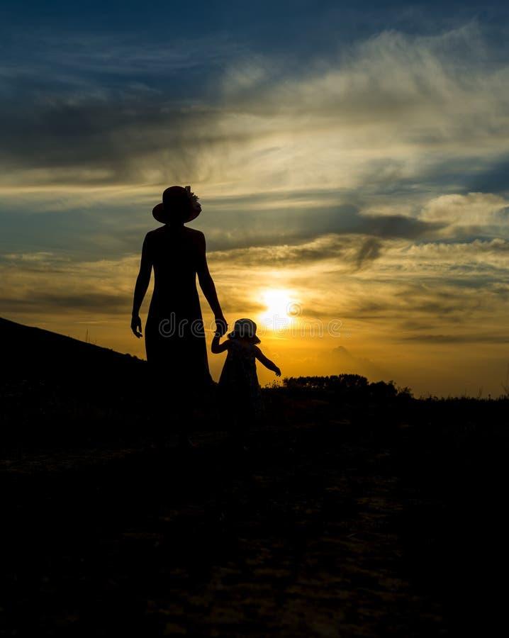 Madre e hija que dan un paseo en la puesta del sol Paisaje hermoso imágenes de archivo libres de regalías