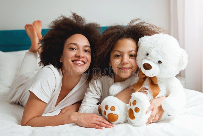 Madre e hija que gozan en la cama, feliz, sonriendo fotos de archivo libres de regalías