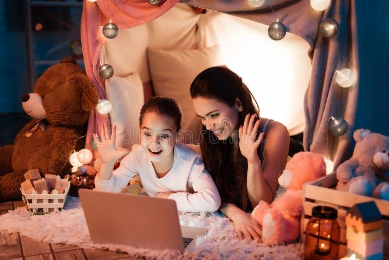Madre e hija que hablan con el padre en el ordenador portátil en casa de la almohada tarde en la noche en casa foto de archivo libre de regalías