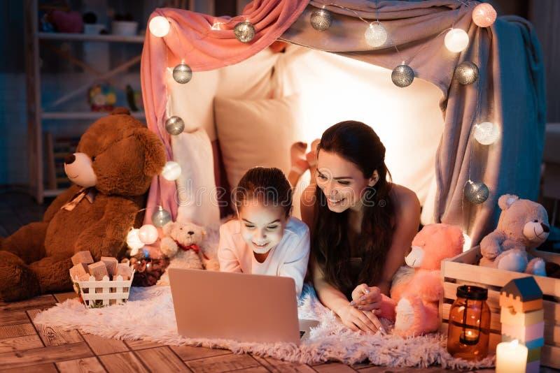 Madre e hija que hablan con el padre en el ordenador portátil en casa de la almohada tarde en la noche en casa imagen de archivo libre de regalías