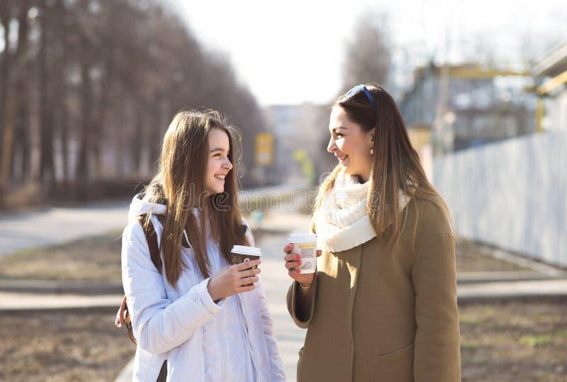 Madre e hija que hablan, sonrisa de risa en la calle, café de consumición en tazas fotos de archivo