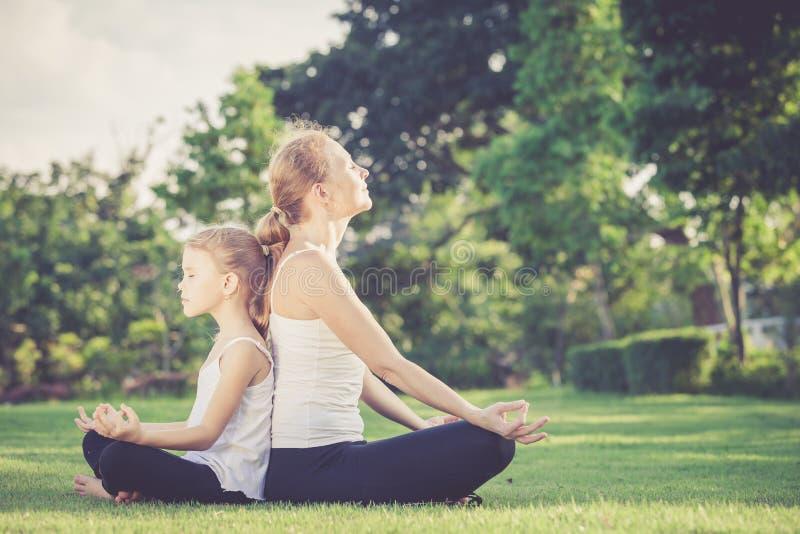 Madre e hija que hacen ejercicios de la yoga en hierba en el parque imagen de archivo
