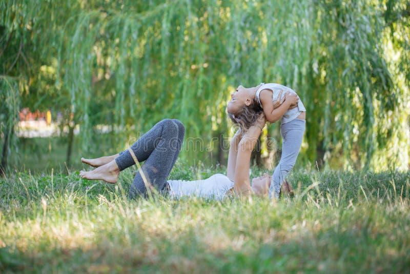 Madre e hija que hacen ejercicios de la yoga en hierba en el parque en el tiempo del día foto de archivo