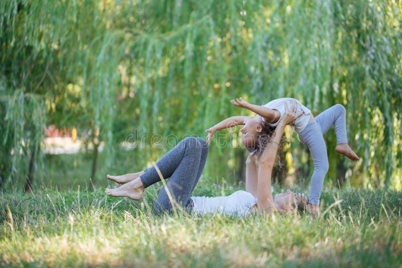 Madre e hija que hacen ejercicios de la yoga en hierba en el parque en el tiempo del día fotografía de archivo
