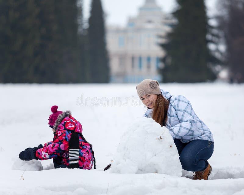 Madre e hija que hacen el muñeco de nieve junto en campo nevoso en la estación del invierno fotos de archivo