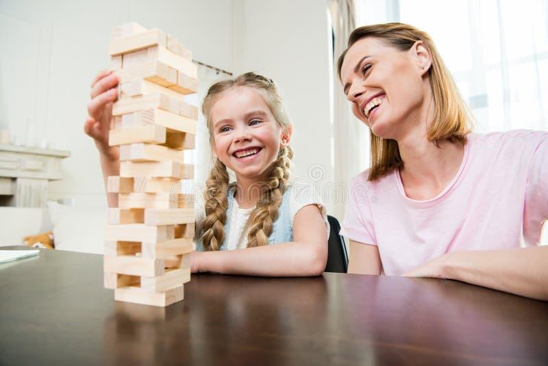 Madre e hija que juegan al juego del jenga junto en casa foto de archivo libre de regalías