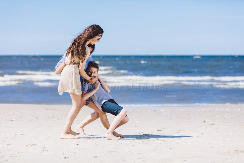 Madre e hija que juegan con el pequeño hermano por el mar foto de archivo