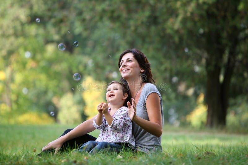 Madre e hija que juegan con la burbuja foto de archivo