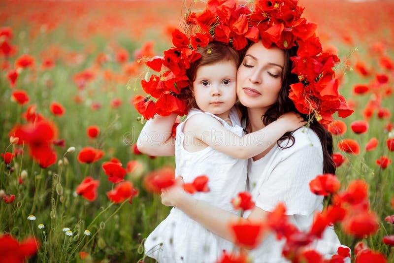 Madre e hija que juegan en campo de flor imagen de archivo libre de regalías