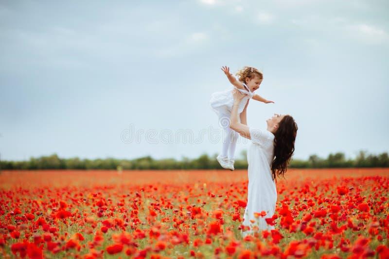 Madre e hija que juegan en campo de flor imágenes de archivo libres de regalías