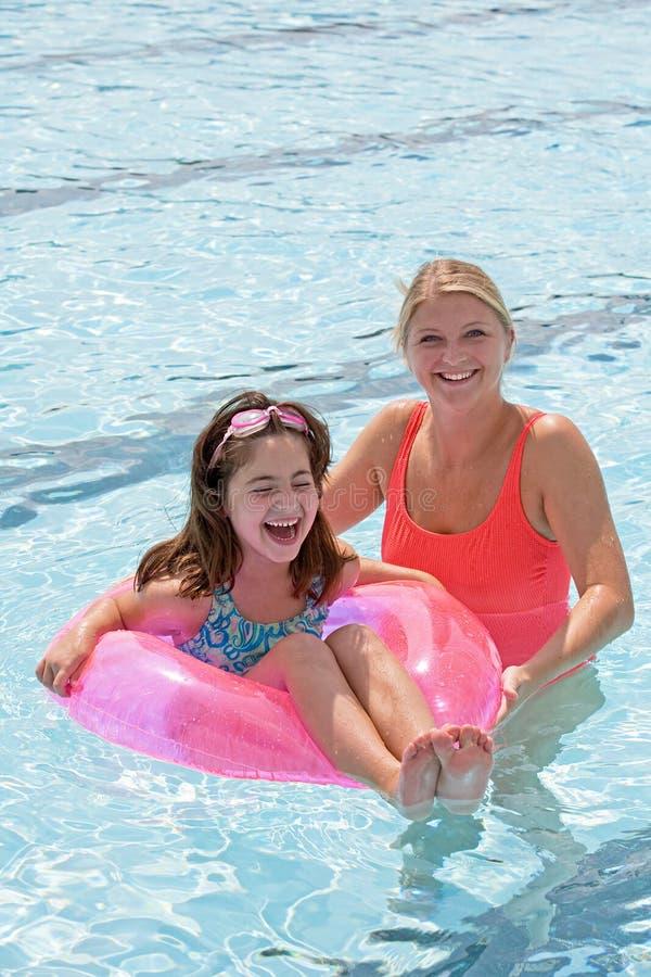 Madre e hija que juegan en la piscina fotografía de archivo