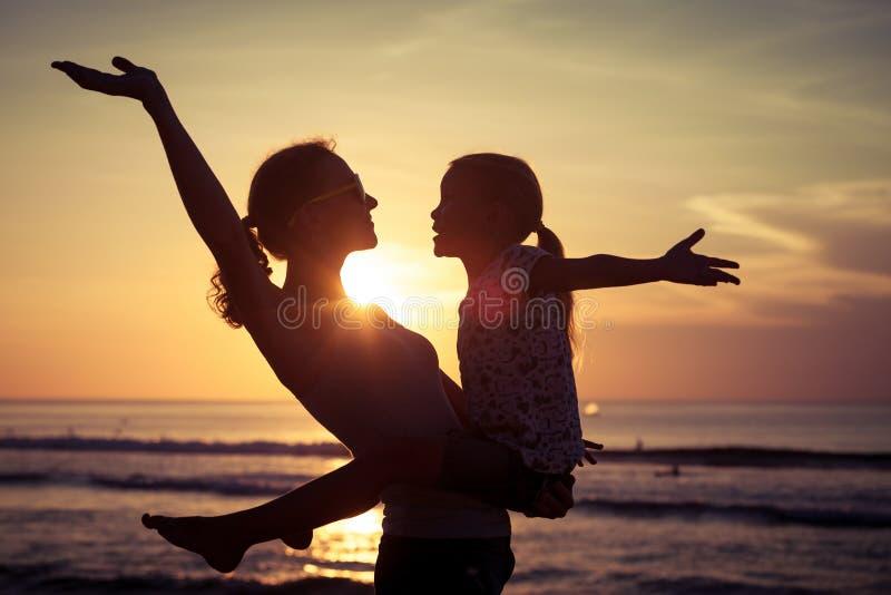 Madre e hija que juegan en la playa en el tiempo de la puesta del sol imagenes de archivo