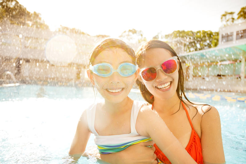 Madre e hija que juegan en piscina foto de archivo libre de regalías