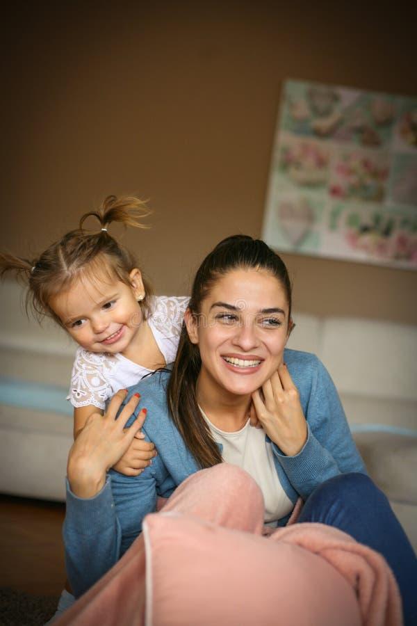 Madre e hija que juegan junto en casa imagenes de archivo
