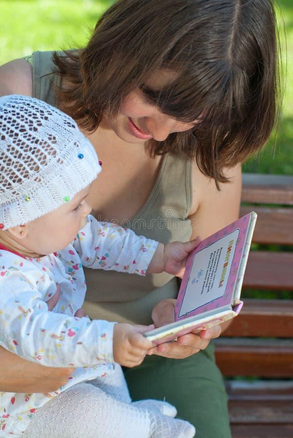 Madre e hija que leen un libro fotografía de archivo