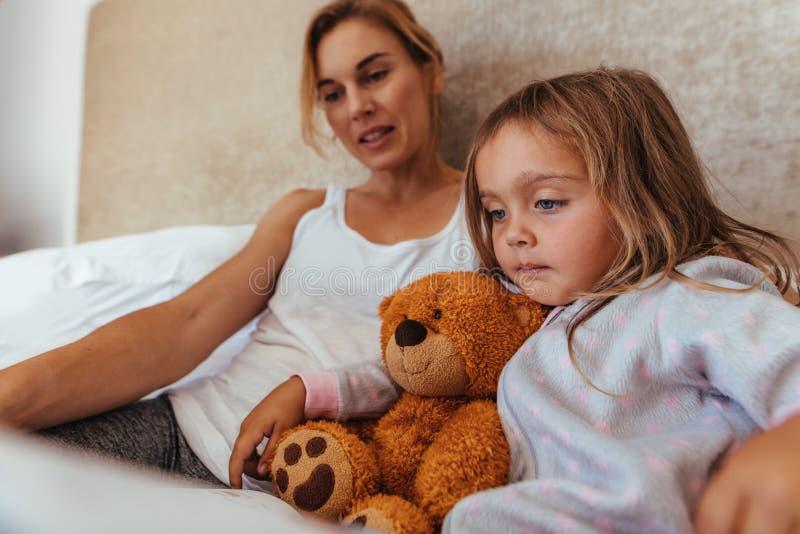 Madre e hija que leen un libro en cama fotografía de archivo libre de regalías