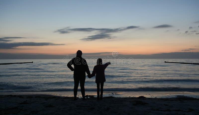 Madre e hija que miran el mar imagenes de archivo