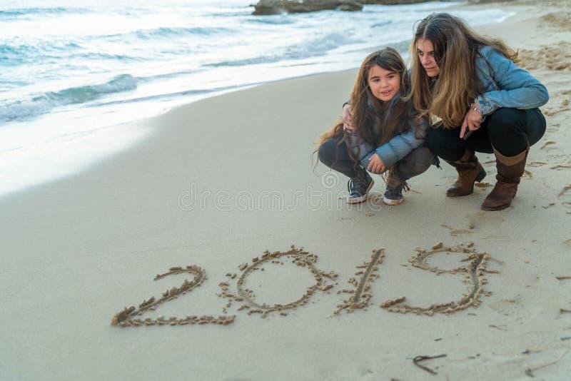 Madre e hija que miran 2019 escrito en la arena fotos de archivo