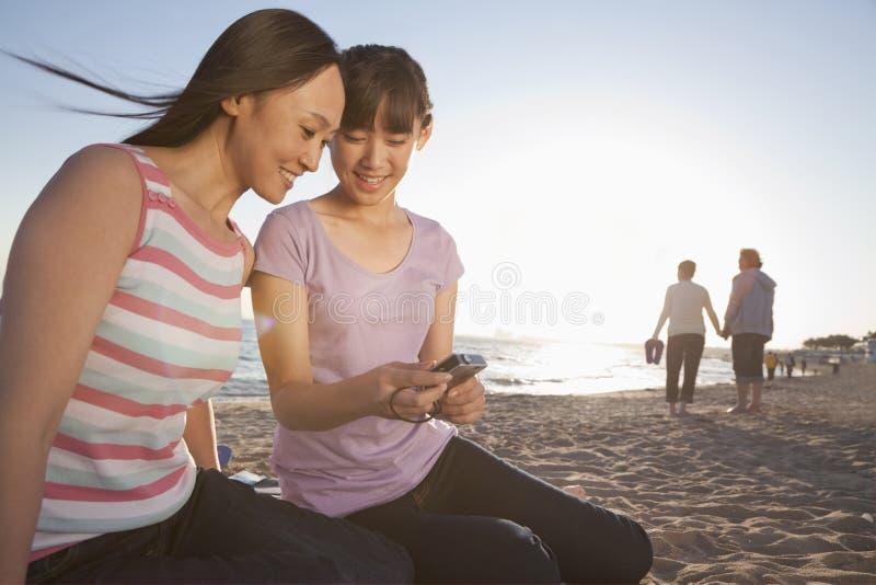 Madre e hija que miran la cámara en la playa imágenes de archivo libres de regalías