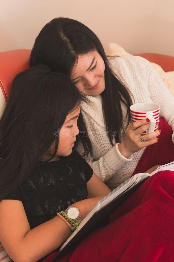 Madre e hija que miran las fotos de familia fotos de archivo