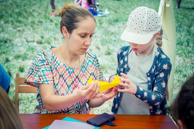 Madre e hija que participan en el taller de la papiroflexia, haciendo figuras de papel coloridas foto de archivo