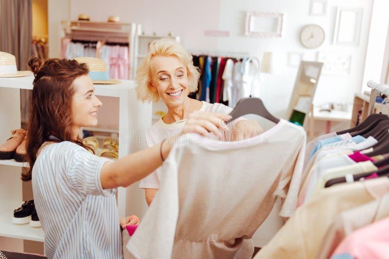 Madre e hija que piensan en la compra del vestido beige fotos de archivo libres de regalías