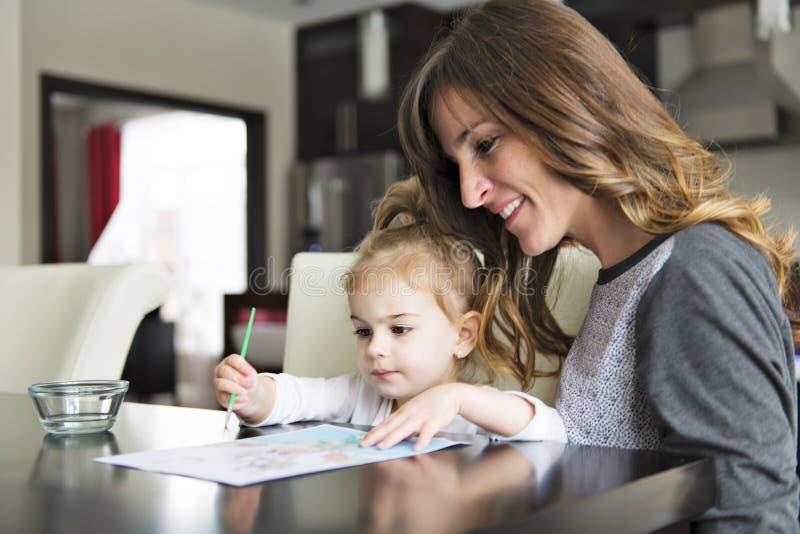 Madre e hija que pintan junto en casa con las brochas y las acuarelas fotos de archivo libres de regalías