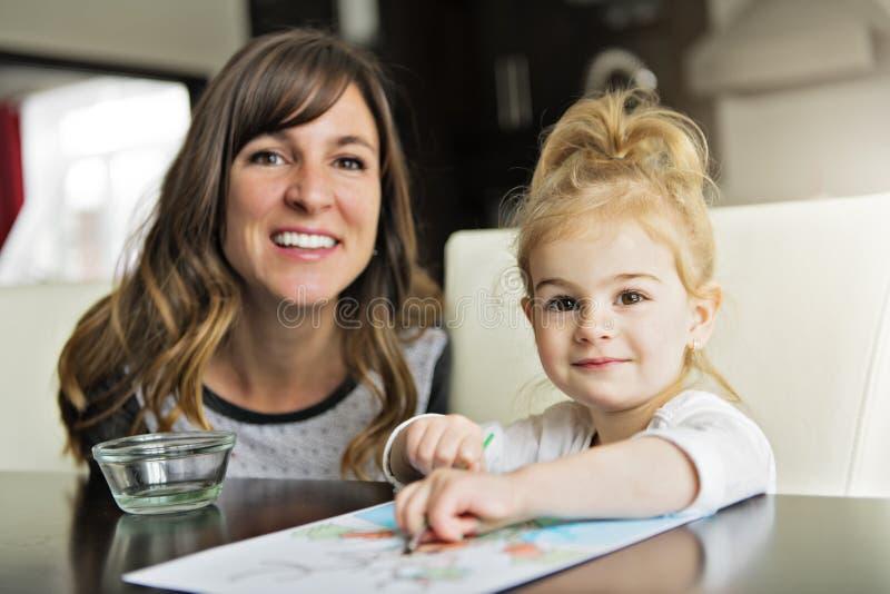 Madre e hija que pintan junto en casa con las brochas y las acuarelas foto de archivo
