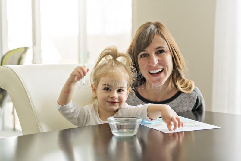 Madre e hija que pintan junto en casa con las brochas y las acuarelas fotografía de archivo