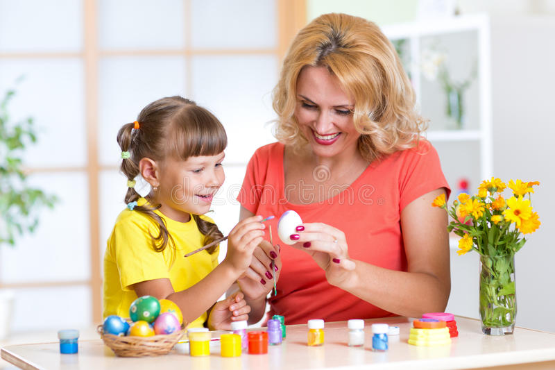 Madre e hija que pintan los huevos de Pascua en casa imágenes de archivo libres de regalías