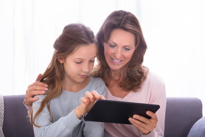 Madre e hija que practican surf en Internet con la tableta de Digitaces foto de archivo