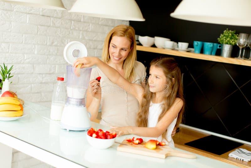 Madre e hija que preparan el jugo sano fotos de archivo libres de regalías