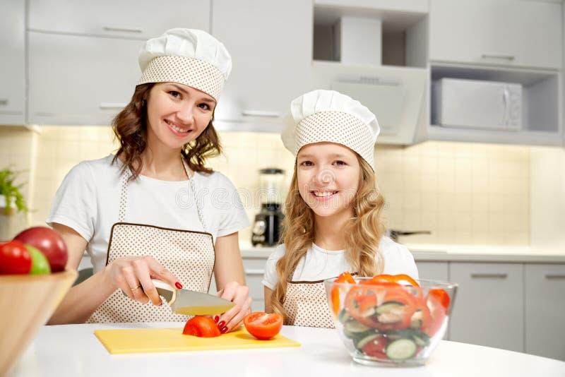 Madre e hija que presentan en la cocina, cocinando la ensalada imágenes de archivo libres de regalías