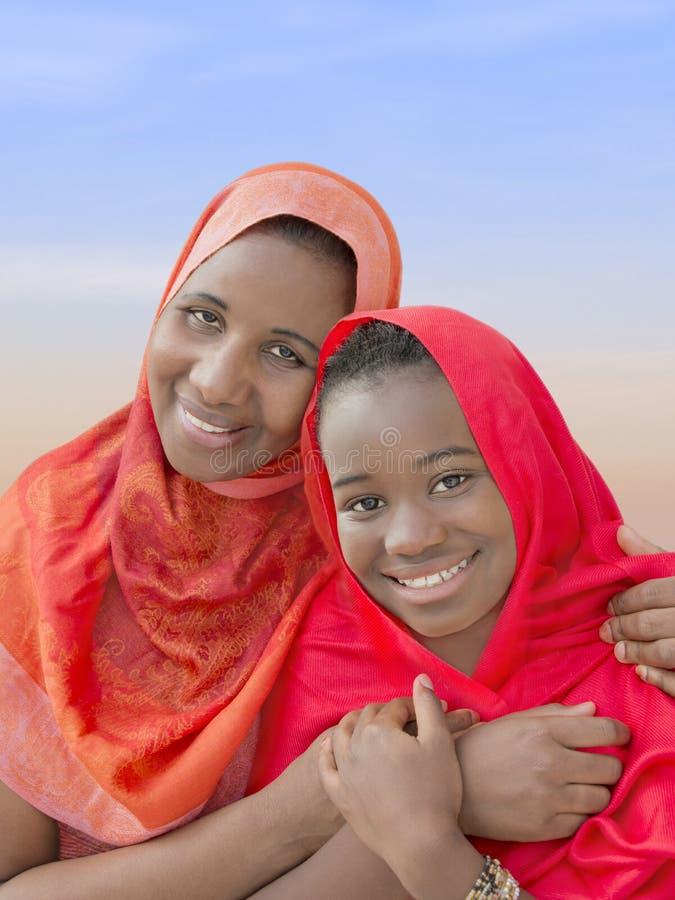 Madre e hija que se abrazan y la sonrisa foto de archivo