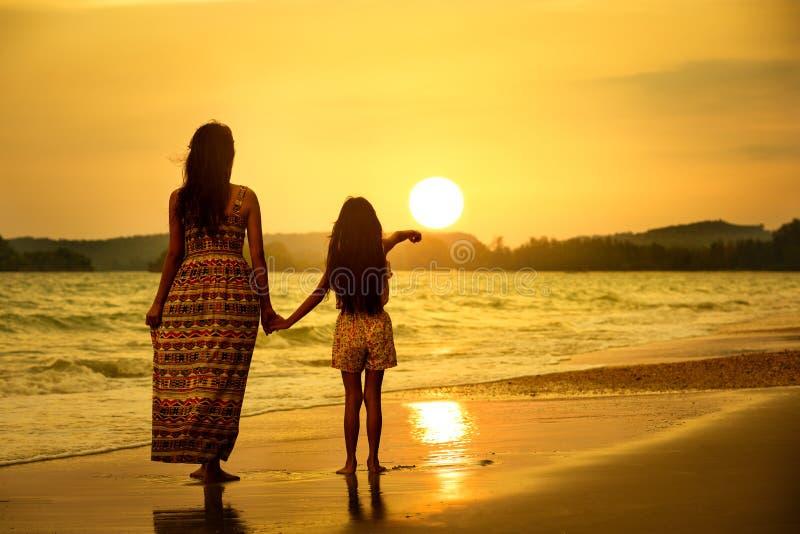 Madre e hija que se colocan en la playa imágenes de archivo libres de regalías