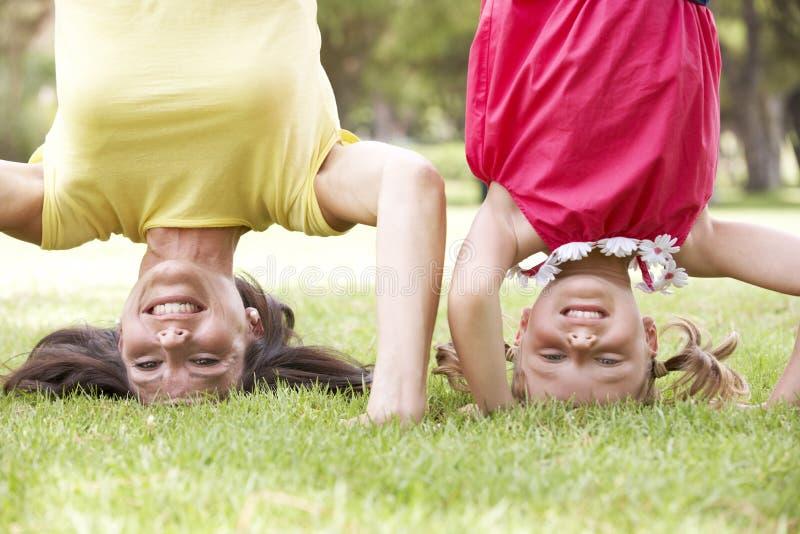 Madre e hija que se colocan en sus cabezas en jardín imagen de archivo libre de regalías