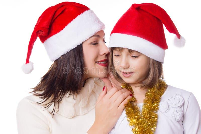 Madre e hija que se comparten secretos el Nochebuena fotografía de archivo