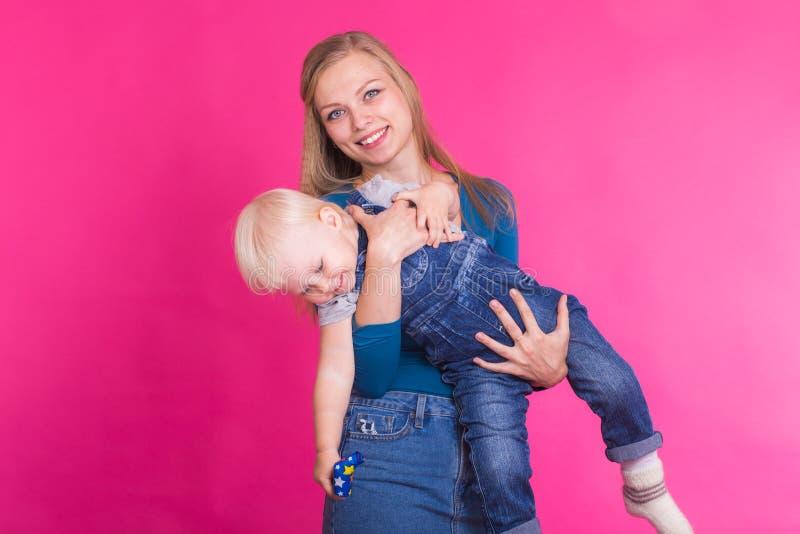 Madre e hija que se divierten aislada en fondo rosado foto de archivo libre de regalías