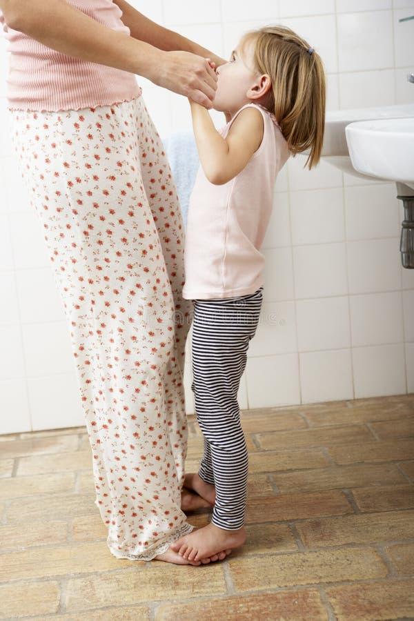 Madre e hija que se divierten en cuarto de baño imagenes de archivo