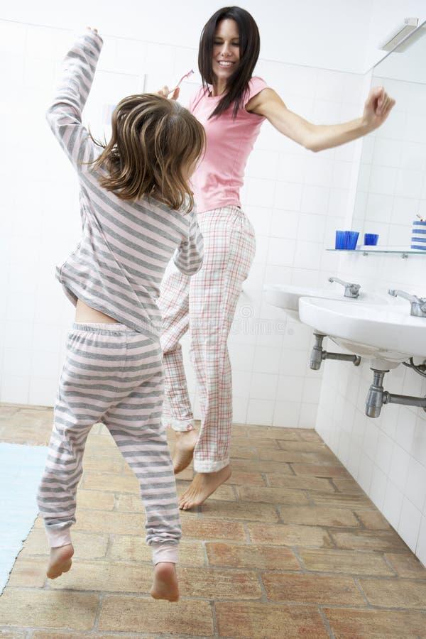 Madre e hija que se divierten en dientes de cepillado del cuarto de baño fotografía de archivo