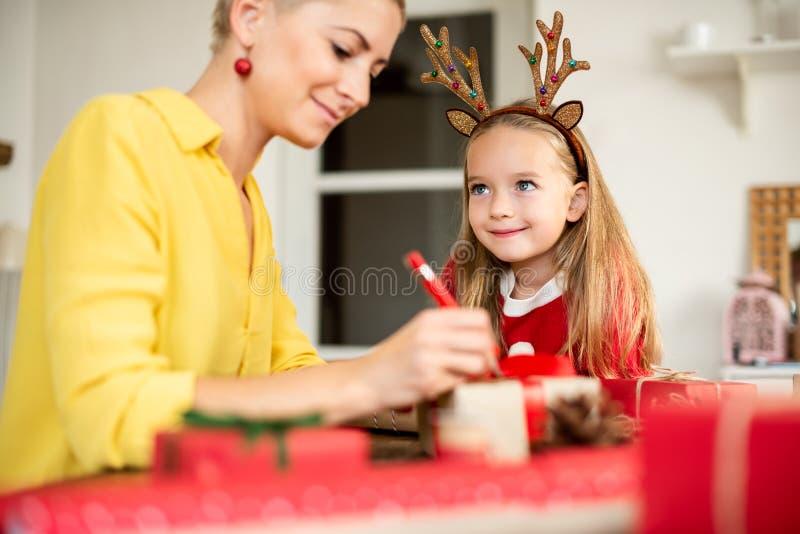 Madre e hija que se divierten que envuelve los regalos de la Navidad juntos en sala de estar Forma de vida sincera del tiempo de  fotografía de archivo