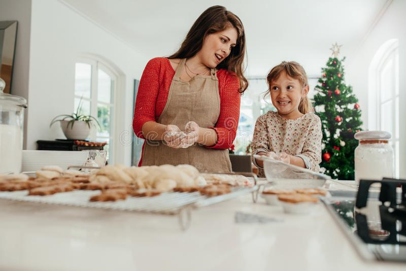 Madre e hija que se divierten mientras que hace las galletas de la Navidad imagen de archivo libre de regalías